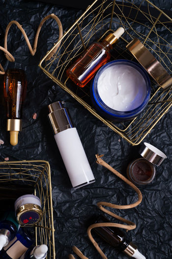 set of nature precious oils and care cosmetics on black background . High Angle View Indoors  No People Choice Still Life Variation Large Group Of Objects Container Directly Above Close-up Table Flame Metal Heat - Temperature Group Paintbrush Group Of Objects Burning Make-up Brush Brush