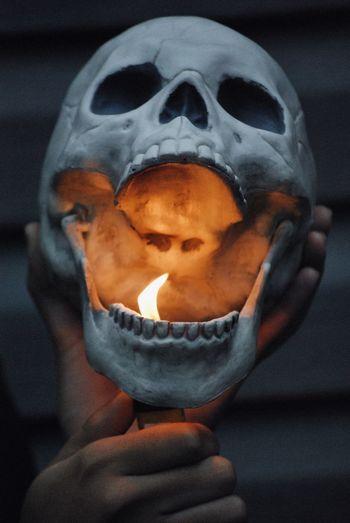 Close-up of hand igniting human skull