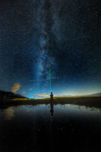 Silhouette Person With Flashlight Standing By Lake Against Star Field At Night