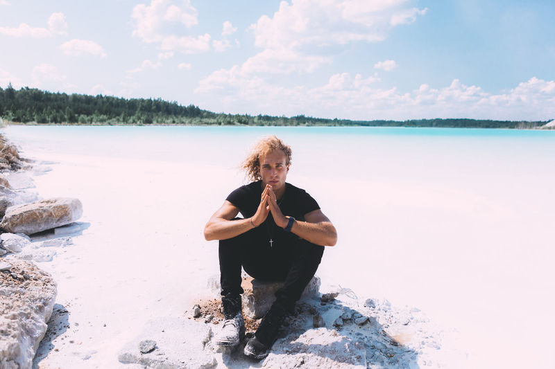 Blond curly guy is sitting on the stone around crystal clear water. Blond trendy hairstyle. Summer time, clear water, clear sky. Adult Beauty In Nature Cloud - Sky Front View Hair Hairstyle Leisure Activity Lifestyles Nature One Person Outdoors Real People Scenics - Nature Sea Sky Tranquil Scene Tranquility Water Young Adult Young Women