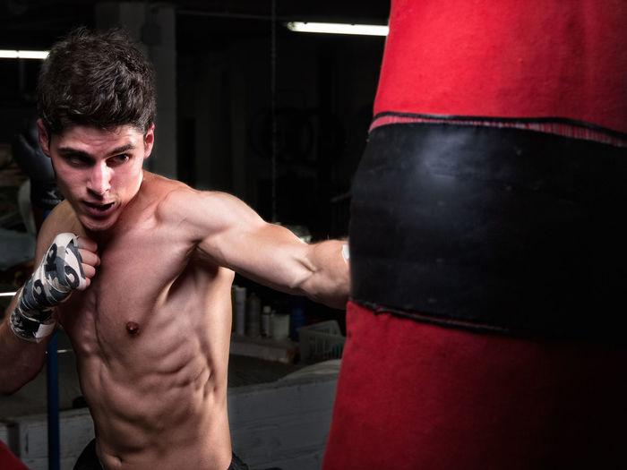 Shirtless Man Punching Bag In Boxing Rink