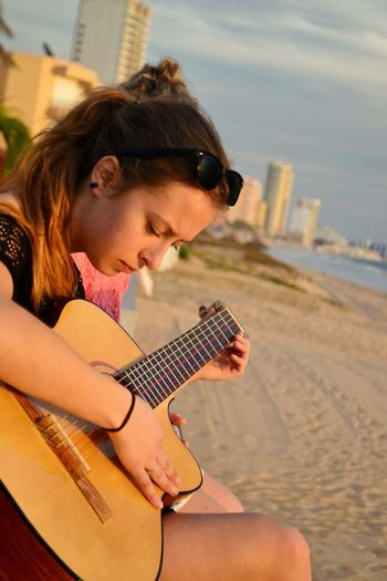 Portrait of woman playing guitar on beach