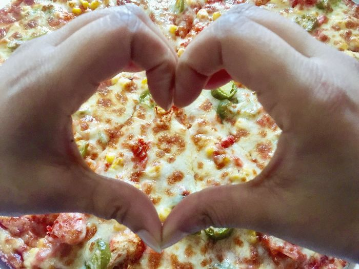 Close-up of hand holding pizza heart