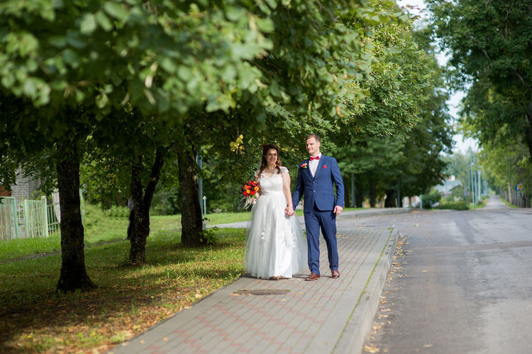 Bride and groom walking at park