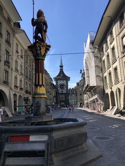 Statue amidst street and buildings against clear sky