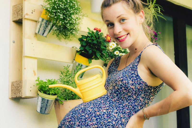 happy pregnant woman with watering can Pregnant Belly  Pregnant Fooling Around Funny Watering Can Florist Watering Balcony Young Woman One Person Child Lifestyles Smiling Happiness Portrait Indoors  Plant Looking At Camera Real People Young Adult Cheerful Emotion