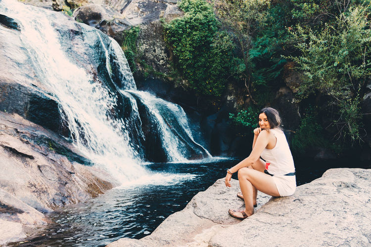 Young woman sitting on rock against waterfall