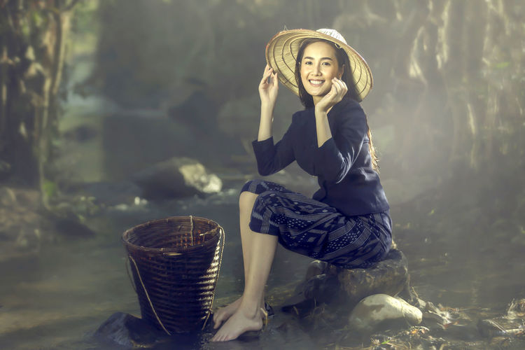 Woman wrapped in fabric sitting on rock