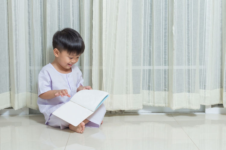 Boy Reading Book While Sitting Against Curtain At Home