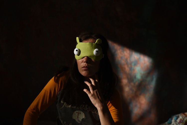Woman wearing sleep mask at home
