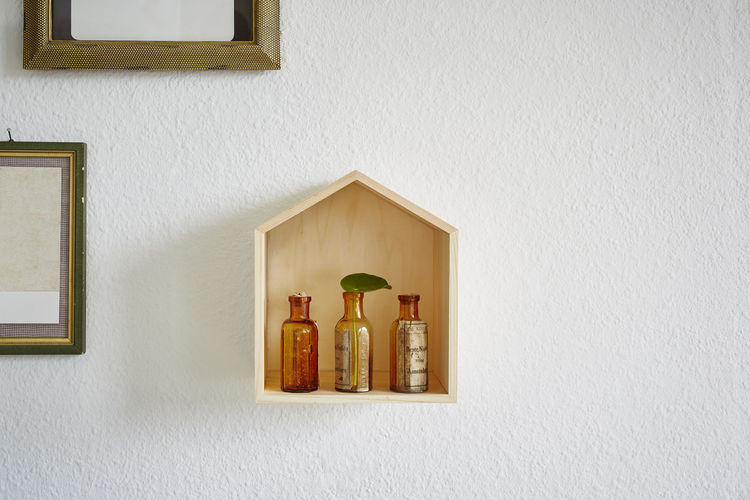 Low angle view of bottles on shelf against wall