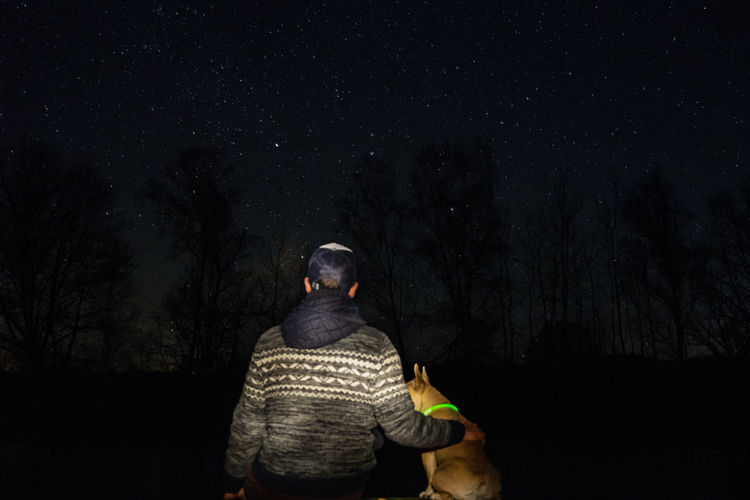 Rear view of man with dog in forest against star field at night