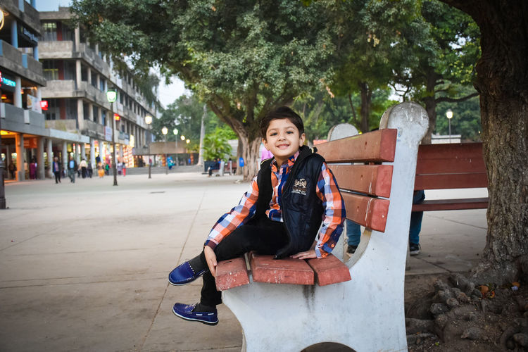 Portrait of cute boy sitting on bench in city