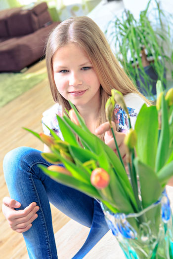 High angle view of teenage girl with flowers in vase on wooden table at home