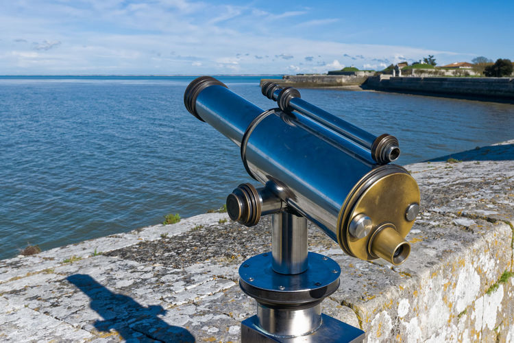 Coin-operated binocular by sea against sky