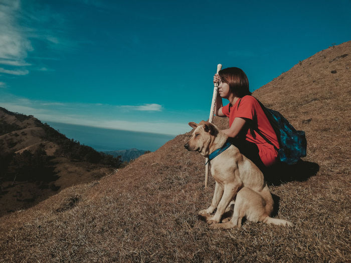 Woman with dog sitting on mountain against sky