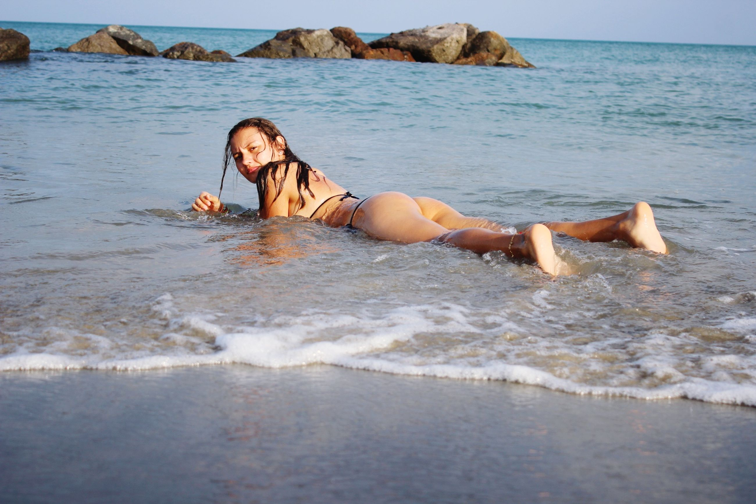 water, sea, beach, lifestyles, leisure activity, vacations, shore, person, young adult, full length, sand, relaxation, horizon over water, young women, wave, summer, shirtless, enjoyment