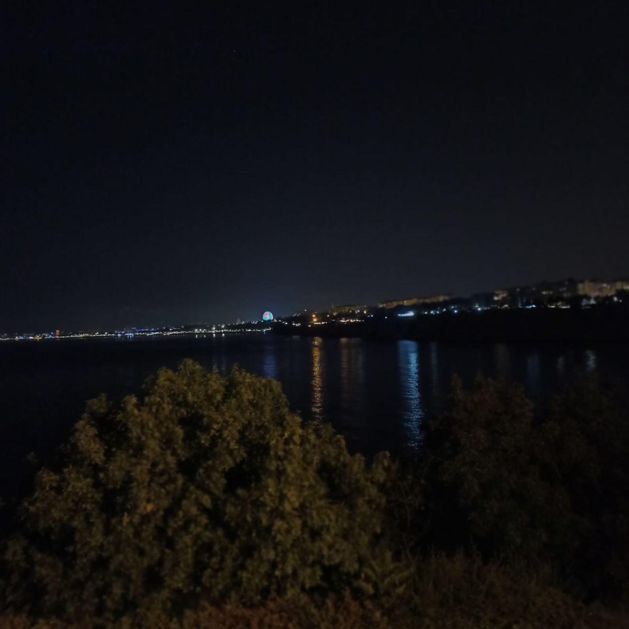 SEA BY ILLUMINATED CITY AGAINST SKY AT NIGHT