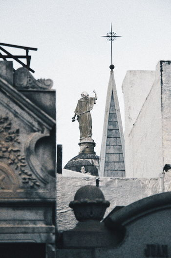 Low angle view of statue against temple against sky