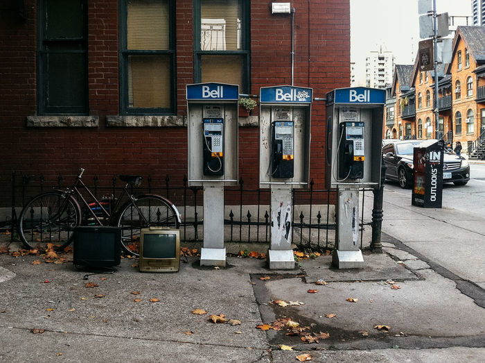 Abandoned television sets by telephone booths on city street against building