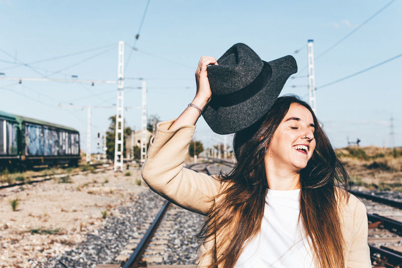 Portrait of beautiful woman in train against sky