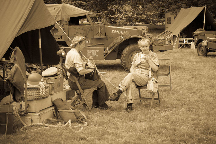 BOCONNOC, LOSTWITHIEL, CORNWALL, ENGLAND, UK - JULY 30, 2016- Women In American World War Two Costume or Dress Sitting Drinking in Army Camp Re-enactment. Sepia and Grain Effect added for Intentional Vintage Filter. Editorial Use Only. American Bivouac Costume Dress Editorial  Female Grain Effect Heritage Historic History Ladies Memorabilia Monochrome People Period Reenactment Retro Tent Vintage War Women World War 2 World War Two WWII Camp First Eyeem Photo The Portraitist - 2017 EyeEm Awards