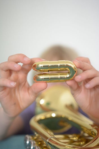 Close-up of person holding gold colored equipment