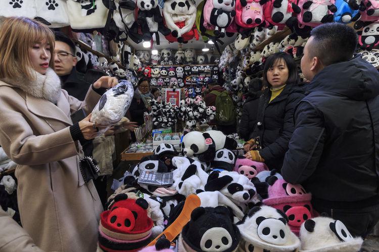 Chengdu, China - December 9, 2018: Chinese tourists buying pandas souvenirs in Chengdu, Sichuan Panda China Sichuan Asian  ASIA Giant Panda Ailuropoda Melanoleuca Chengdu Zoo Bamboo Habitat Animal Bear Endangered Species Souvenir Store Shore