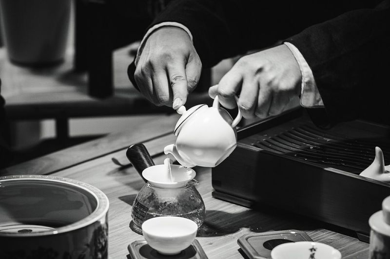 Cropped Image Of Hands Pouring Tea In Pot On Table