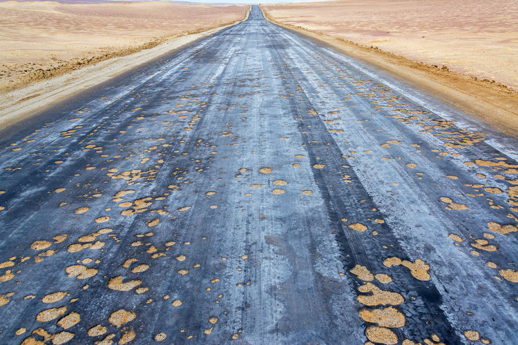Empty Damaged Country Road On Landscape