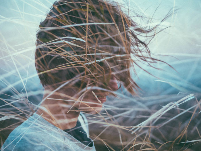 Double Exposure Of Grass And Woman With Tousled Hair