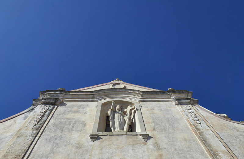 Low angle view of statue by church facade against clear blue sky