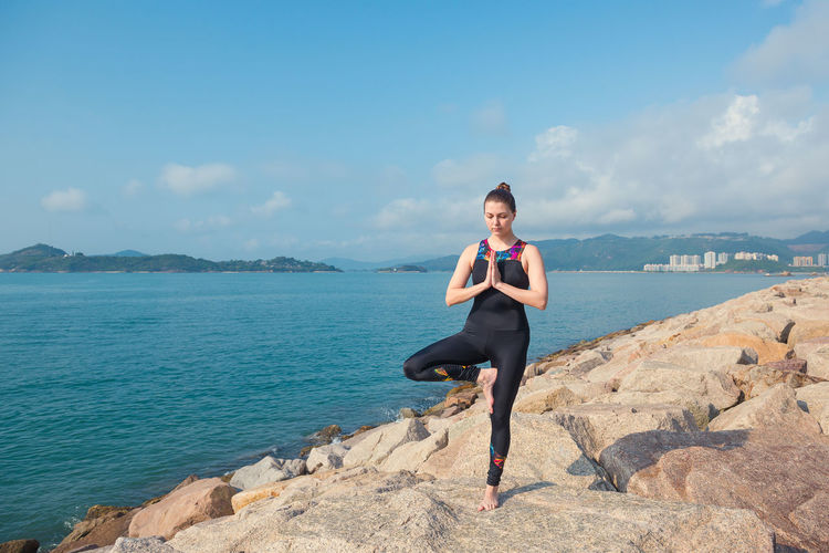 Full Length Of Woman Doing Yoga On Rock By Sea Against Sky