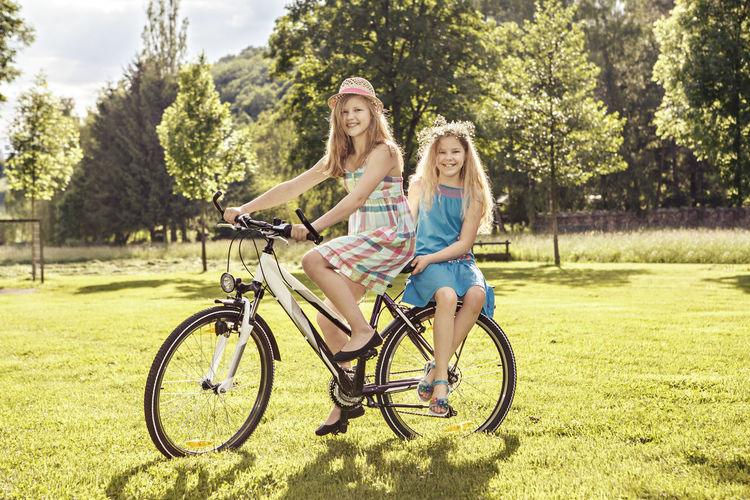 Woman and girl riding bicycle on grass against trees