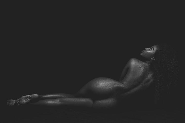 Man lying down against black background