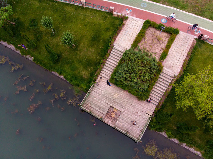 People cycling on the path at the riverside. Plant High Angle View Green Color Water Growth Day Nature No People Tranquility Grass Beauty In Nature Outdoors Wood - Material Land Scenics - Nature Lake Tranquil Scene Field Tree Swimming Pool Bycle Top View Dronephotography Pier Riverside
