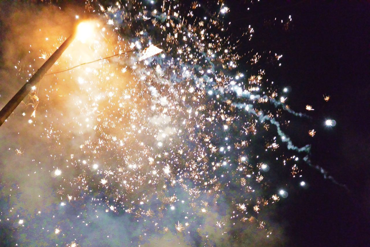 night, celebration, firework display, event, illuminated, firework - man made object, low angle view, arts culture and entertainment, exploding, glowing, long exposure, outdoors, smoke - physical structure, multi colored, blurred motion, no people, firework, motion, sky