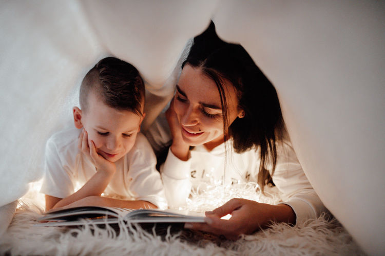Mother and woman reading book on bed