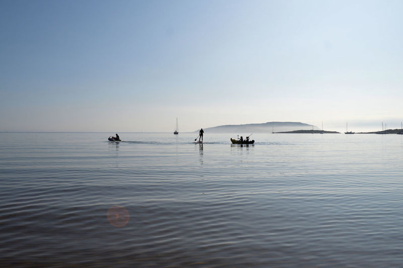 Scenic view of people playing in the sea against clear sky