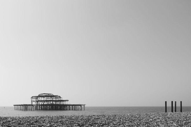 Silhouette brighton pier in sea against sky