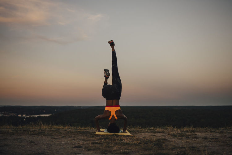 Full length of woman with arms raised against sky during sunset