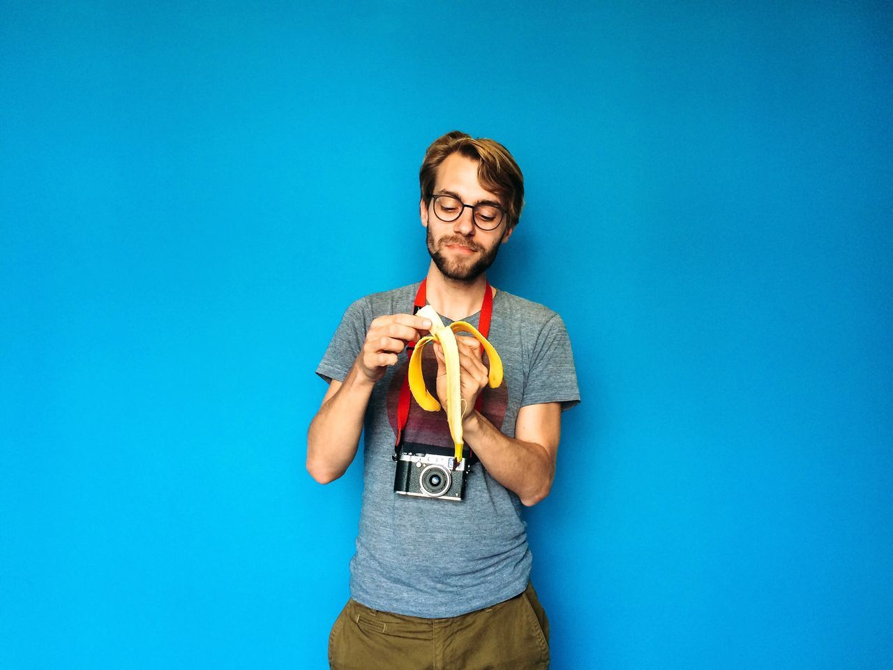 PORTRAIT OF HIPSTER MAN STANDING IN FRONT OF BLUE WALL