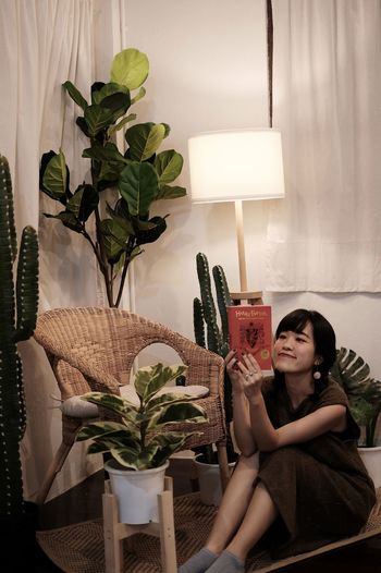 Portrait of young woman sitting on potted plant