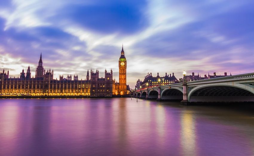 Illuminated Big Ben Tower By Parliament Building And Bridge Against Sky During Sunset