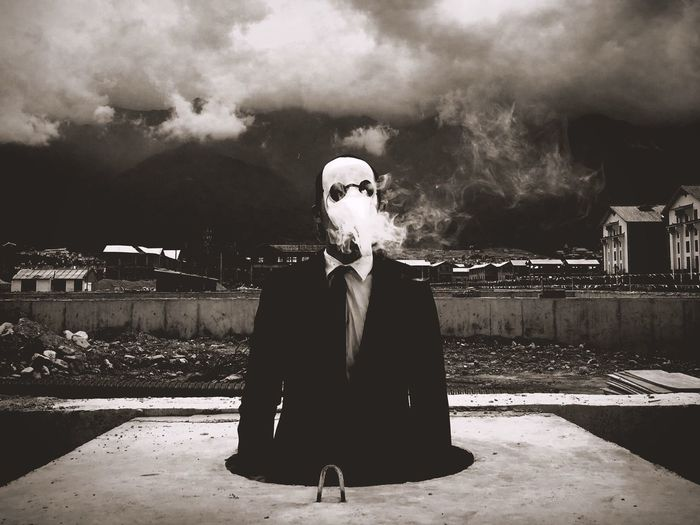 Businessman wearing mask standing in storage tank while smoking against cloudy sky