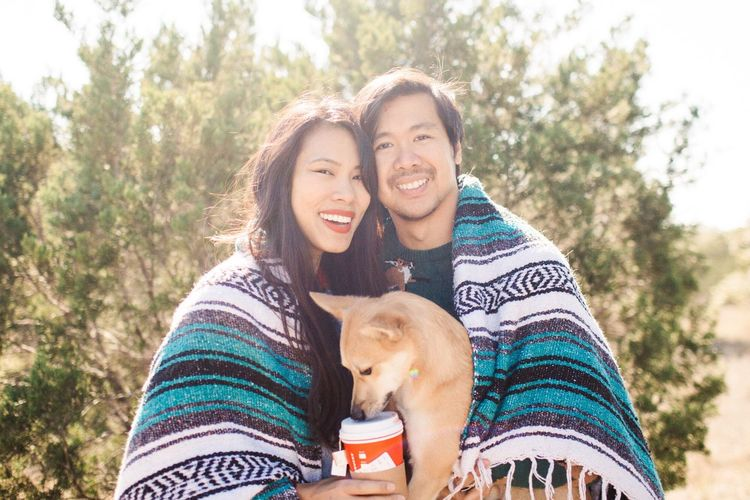 Portrait of a smiling couple with dog covered in blanket
