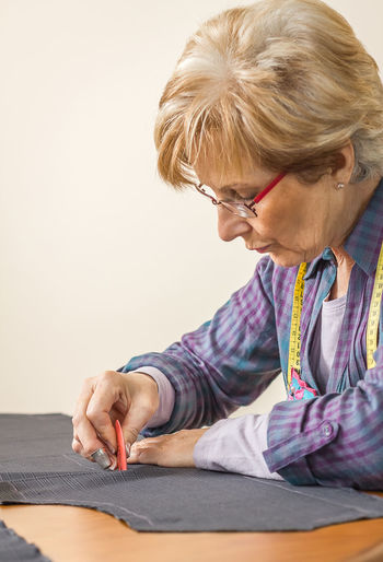 Midsection of woman holding eyeglasses while sitting on table