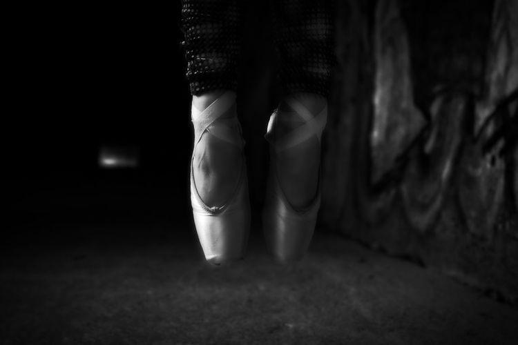 Low section of ballet dancer in darkroom