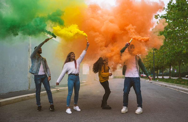 Carefree friends holding distress flares while standing on road