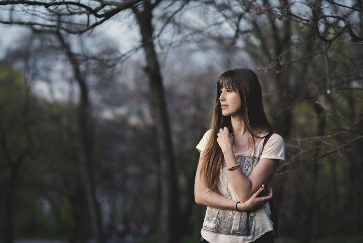 beautiful young woman outside in the girl with long brown hair in thoughtful pose Beautiful Woman Casual Clothing Contemplation Day Focus On Foreground Forest Front View Hair Hairstyle Land Leisure Activity Lifestyles Long Hair Nature One Person Outdoors Plant Real People Standing Teenager Tree Young Adult Young Women